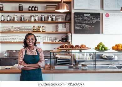 Portrait of a smiling young African female entrepreneur standing with her arms crossed at the counter of her bistro