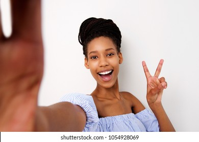 Portrait of smiling young african girl making peace sign selfie against white background