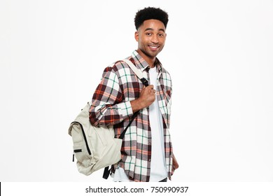 Portrait of a smiling young african male student dressed in plaid shirt with a backpack looking at camera isolated over white background