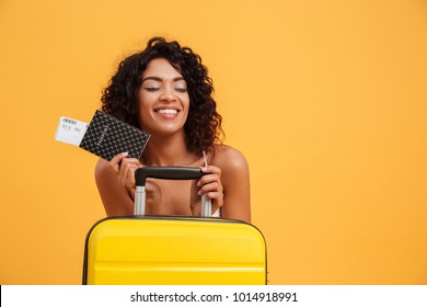 Portrait of a smiling young african woman dressed in summer clothes holding passport with flying tickets while standing with a suitcase isolated over yellow background