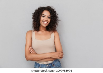Portrait of a smiling young african woman standing with arms folded over gray background
