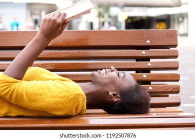 Portrait of smiling young african woman lying on bench reading book