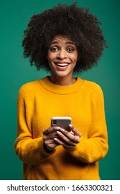 Portrait of a smiling young african woman wearing sweater standing isolated over green background, using mobile phone