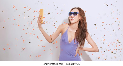 Portrait of a smiling young african woman taking selfie with mobile phone over white background with confetti.