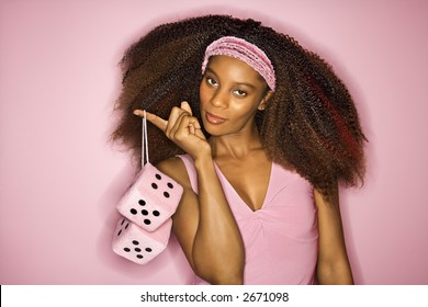 Portrait of smiling young African-American adult woman on pink background holding fuzzy dice.