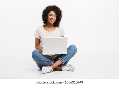 Portrait of smiling young afro american woman using laptop while sitting on a floor with legs crossed isolated over white background
