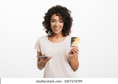 Portrait of a smiling young afro american woman holding mobile phone and showing credit cards isolated over white background