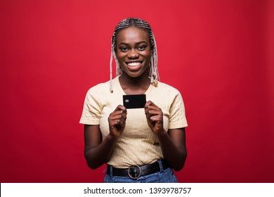Portrait of a smiling young afro american woman holding mobile phone and showing credit cards isolated on red background