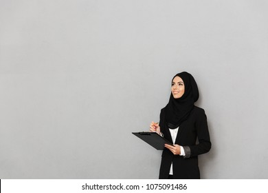 Portrait of a smiling young arabian woman holding clipboard with documents isolated over gray background