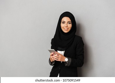 Portrait of a smiling young arabian woman holding mobile phone isolated over gray background