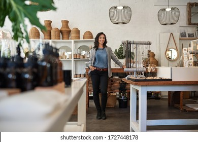 Portrait of a smiling young Asian business owner standing by a counter in her trendy shop