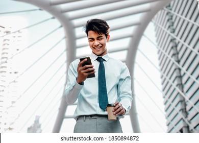 Porträt eines lächelnden jungen asiatischen Geschäftsmanns, der Mobiltelefon in der Stadt verwendet