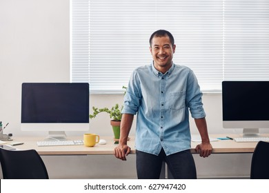 Portrait of a smiling young Asian designer leaning on a computer table while standing alone in a modern office
