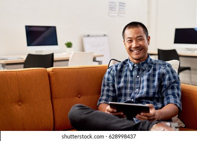Portrait of a smiling young Asian designer working online with a digital table while sitting alone on a sofa in a large modern office