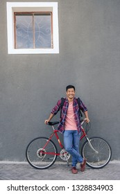 930ec8178 Portrait of a smiling young Asian man in a plaid shirt standing with his  bike in