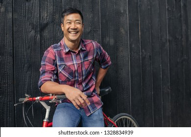 e892ee25d Portrait of a smiling young Asian man in a plaid shirt sitting on his bike  leaning
