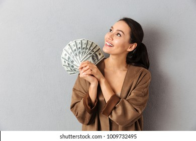 Portrait of a smiling young asian woman holding bunch of money banknotes and looking away over gray background