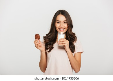 bf4faaac165 Portrait of a smiling young asian woman eating cookie and holding glass of  milk isolated over