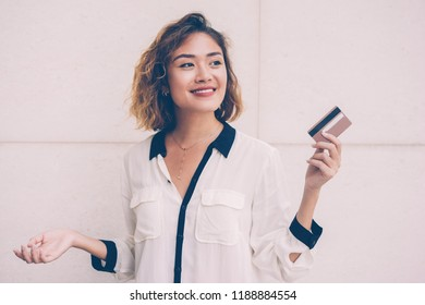 Portrait of smiling young Asian woman showing credit card. Female cardholder planning shopping. Finance and banking concept