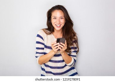 Portrait of smiling young asian woman holding cellphone by gray wall