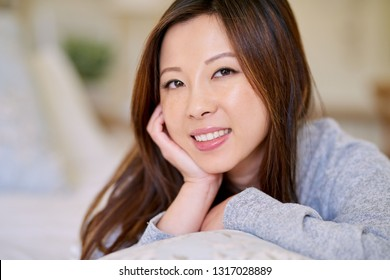 Portrait of a smiling young Asian woman with a perfect complexion and long hair lying on her bed with her hand on her chin