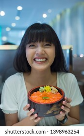 Portrait of smiling young asian woman holding japanese food in restaurant