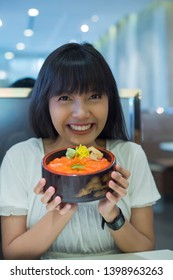 Portrait of smiling young asian woman holding japanese food bowl in restaurant