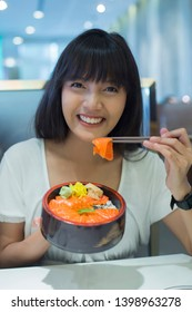 Portrait of smiling young asian woman eating japanese food in restaurant