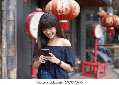 Portrait of smiling young asian woman holding smart phone in front of chinese restaurant