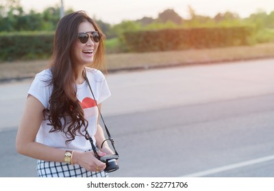 Portrait of smiling young Asian woman traveler photography hipster lifestyle stay on the road with camera