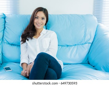 A portrait of smiling young Asian woman sitting relax on sofa at living room