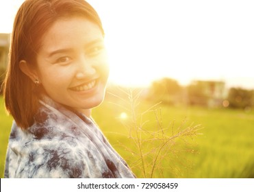 Portrait of smiling young Asian woman with sunlight flare. Pretty cheerful woman looking at camera with joyful and charming smile. Young girls relaxing in summer sunset  outdoor, copy space