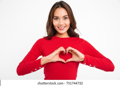 Portrait of a smiling young asian woman showing heart gesture with two hands and looking at camera isolated over white background