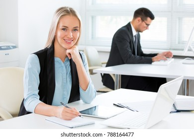 Portrait of a smiling young attractive business woman in an office