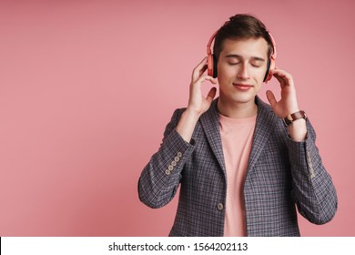 Portrait of a smiling young attractive man wearing jacket standing isolated over pink background, lstening to music with wireless headphones