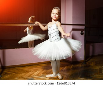 Portrait of smiling young ballerina in white tutu and pointes posing isolated in dance studio. Small balet dancer standing near bar and mirror, preparing for perfomance.