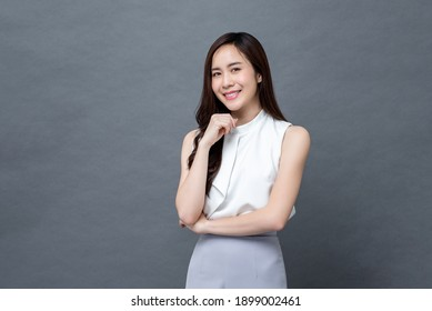 Portrait of smiling young beautiful Asian businesswoman looking at camera in isolated studio gray background