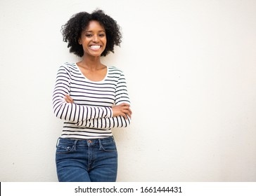 Portrait smiling young beautiful black woman with arms crossed isolated white background