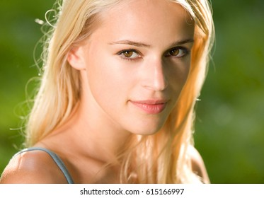 Portrait of smiling young beautiful blond woman, outdoors