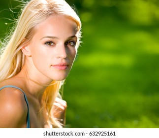 Portrait of smiling young beautiful blond woman outdoors, with copyspace