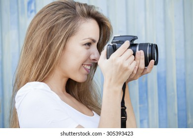 Portrait of smiling young beautiful girl taking a photo