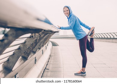 Portrait of smiling young beautiful woman looking at camera, wearing sportswear, leaning on railing, holding and stretching leg on bridge outdoors. Side view.