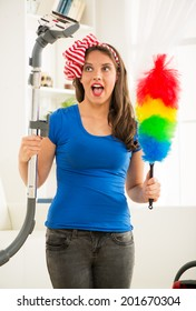 Portrait of a smiling young beautiful woman cleaning house.