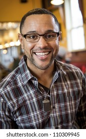 Portrait of smiling young black man in the interior of coffee shop.