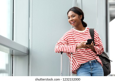 Portrait of smiling young black woman waiting at airport with mobile phone and bags