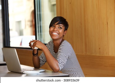 Portrait of a smiling young black woman with coffee and laptop at cafe