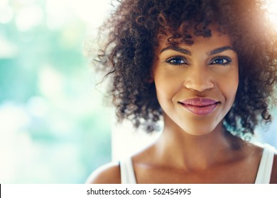 Portrait of smiling young black woman with sunlight flare and copy space