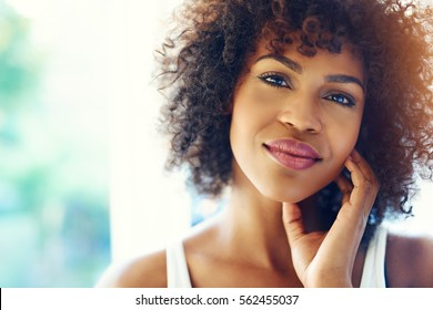 Portrait of smiling young black woman in sunshine with chin on hand and copy space