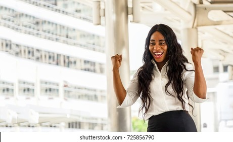 Portrait of smiling young black woman ,Business woman hands up happy in the success office background, Business Concept.