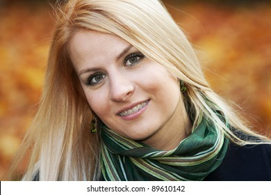Portrait of smiling young blond woman over autumnal background
